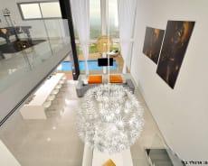 מבט מהקומה העליונה על הסלון, שימו לב שבוילה אקווה בוטיק התקרה גבוהה - וילה AQUA בוטיק